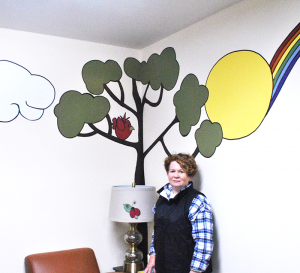 "Volunteer and ""artist in residence"" Jo Beth Lehrer by part of the mural she created for HOPE's youth counseling room."