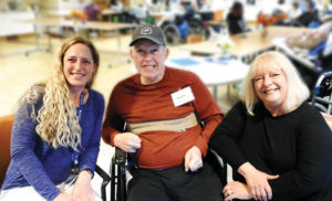Donna Rawon, right, is the primary caregiver for her husband, Ralph Rawson. In 2016, he had his second stroke, which impacted his entire right side, including his ability to eat and swallow. Last January, he had another stroke (his third) that affected his peripheral vision. Next to them is Sara Spinner, program director, The Adult Day Center at St. Camillus, where Ralph is a registrant. Photo courtesy of Deborah Christiansen, The Centers at St. Camillus.