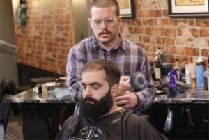 Taylor Horsman, a barber at Saving Face in Manlius. cutting the hair of one of his clients.